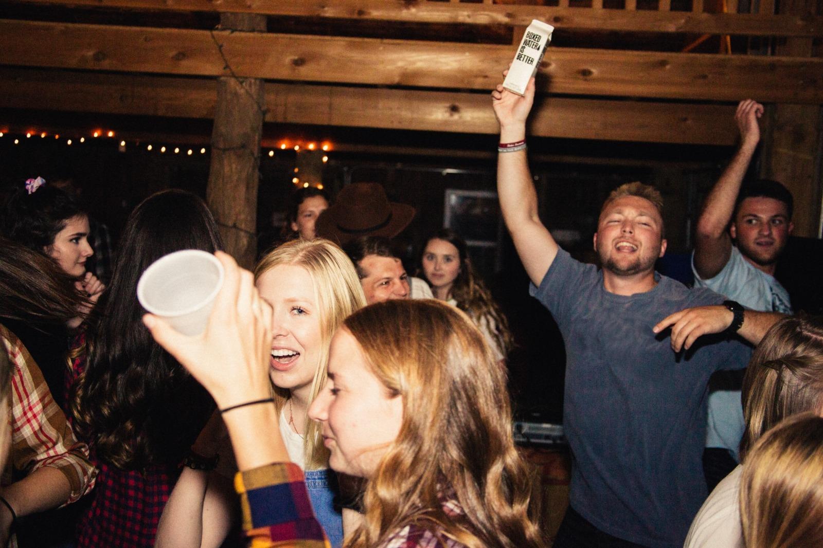 tineri care danseaza si beau in club