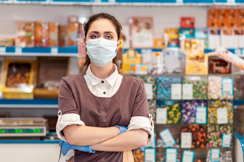 Angajat al unui magazin purtând mască
