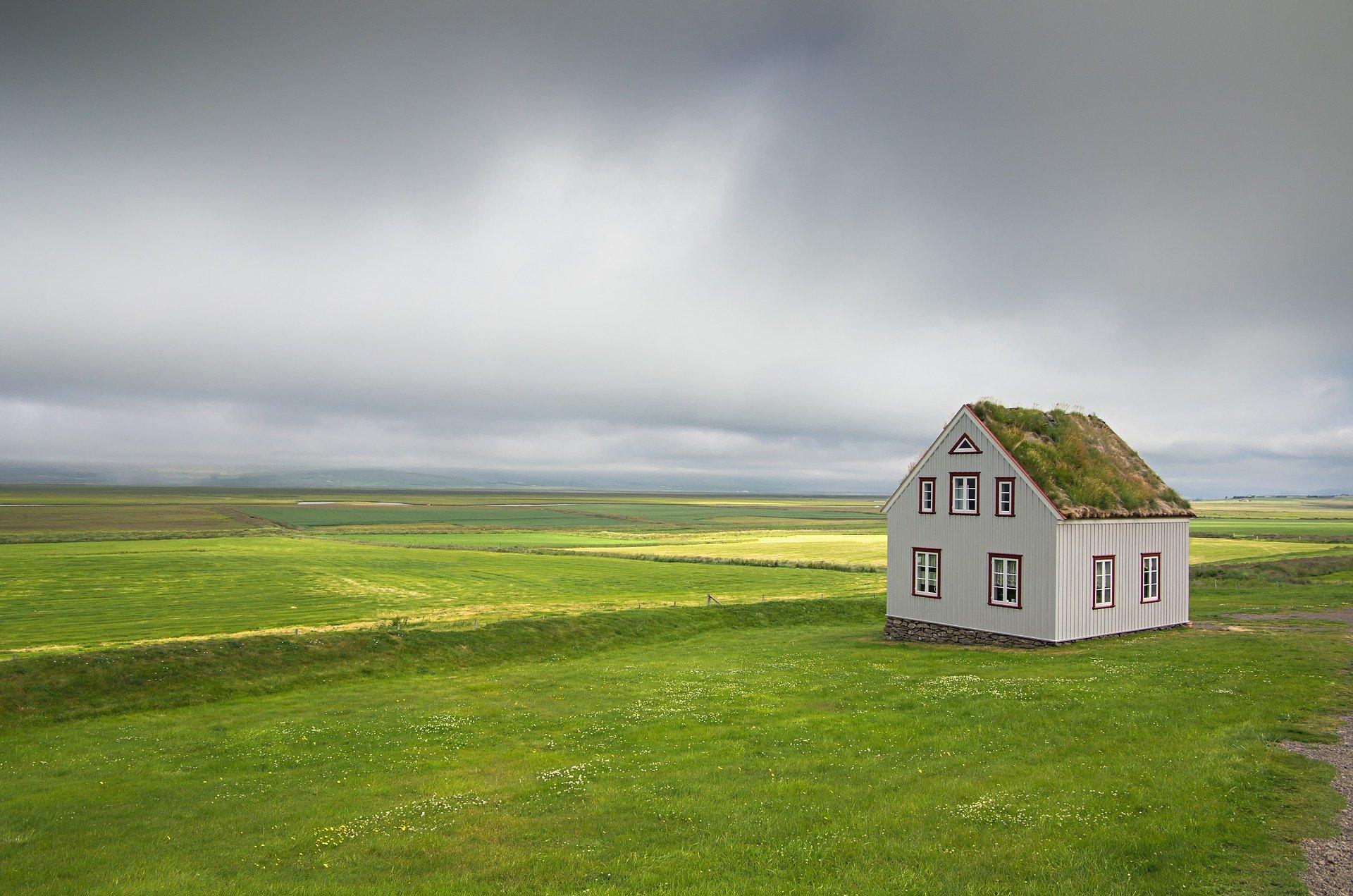 Casa cu acoperis din tigla metalica, amplasata pe un camp