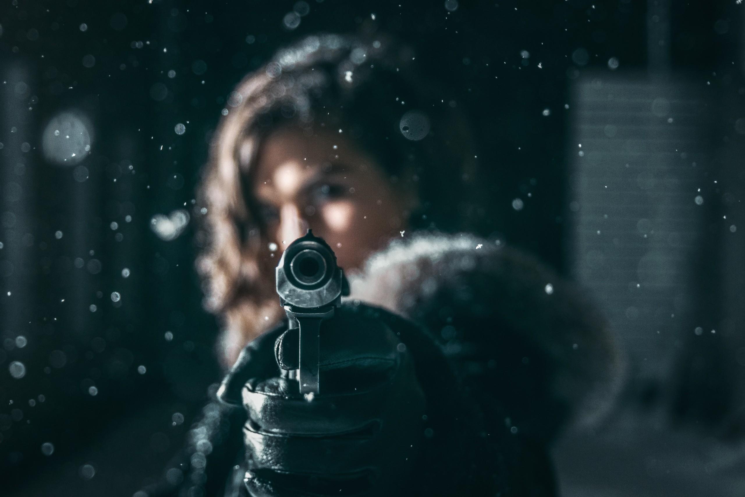 Pistol in prim-plan tinut de o fata