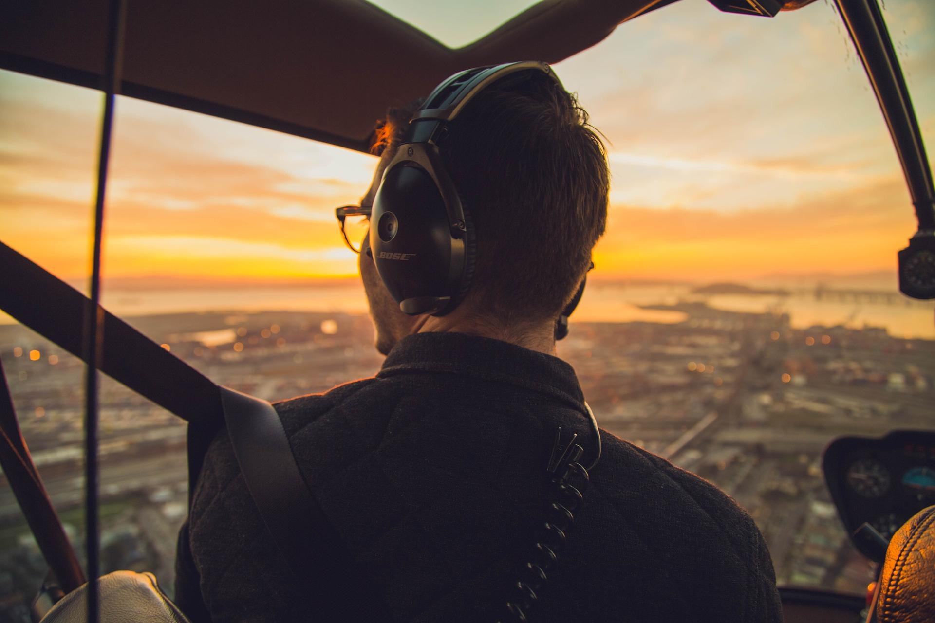 Pilot in elicopter cu peisaj de sus la apusul soarelui
