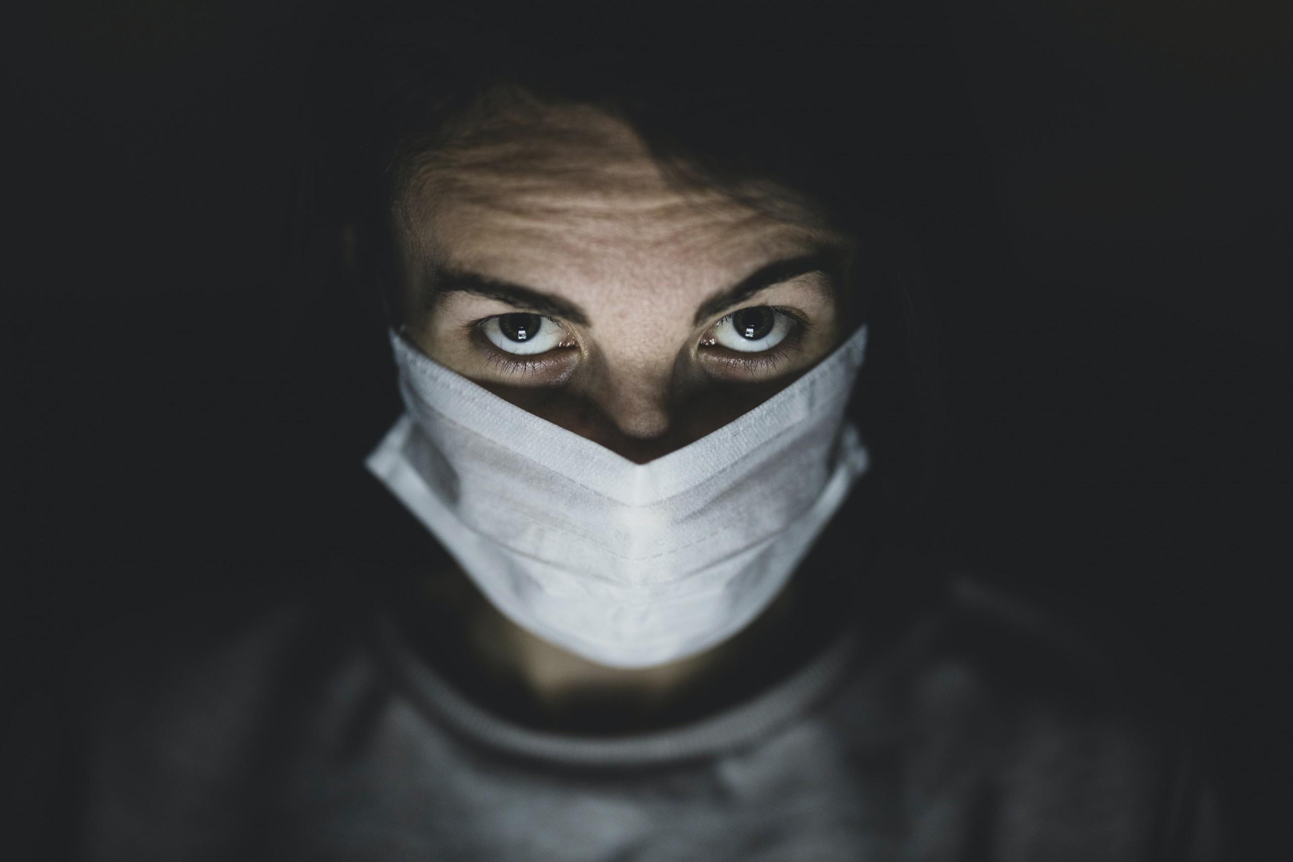 Barbat cu mască ce privește spre cameră