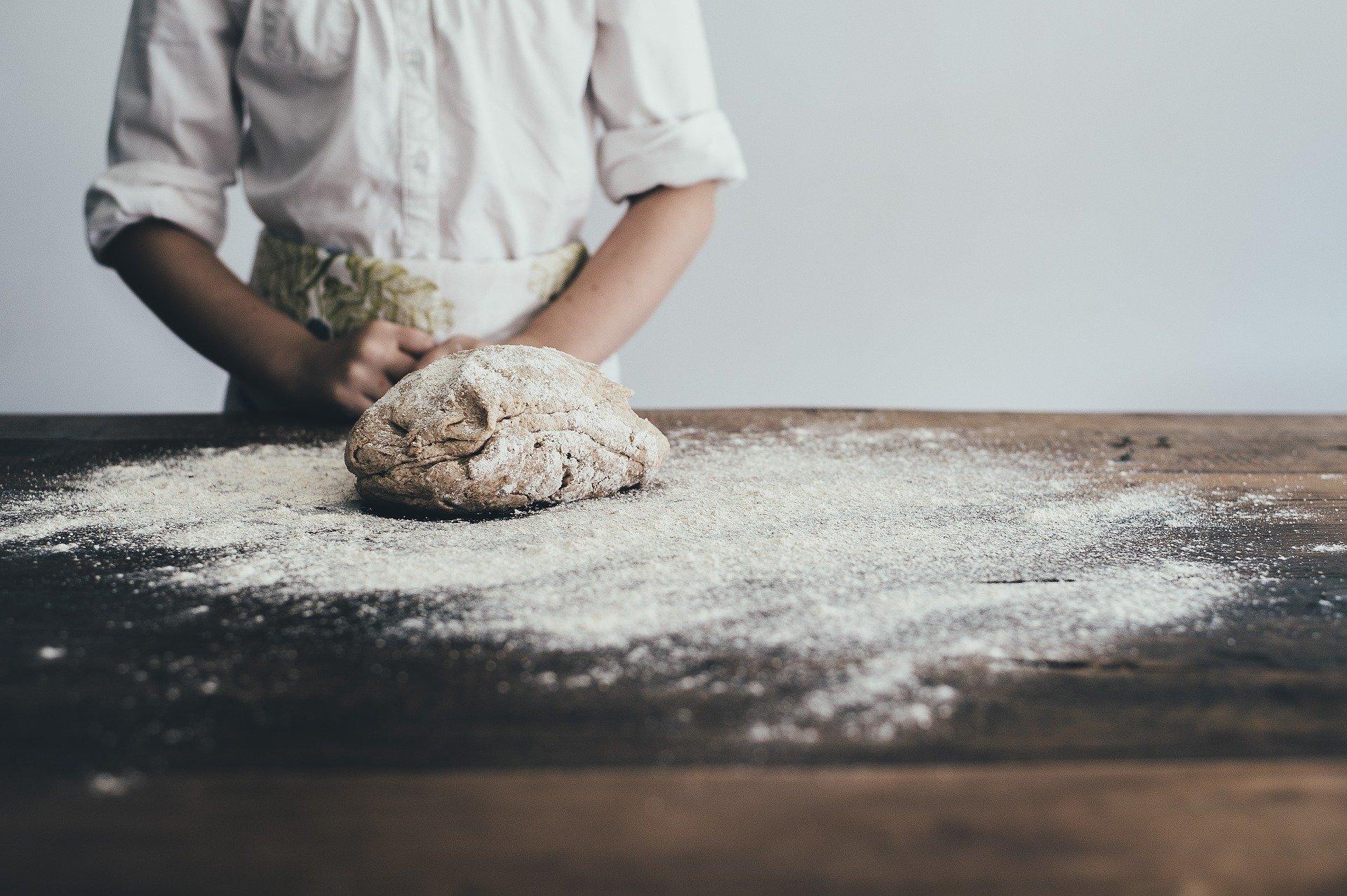 Brutar lângă o masă unde se află o pâine necoaptă