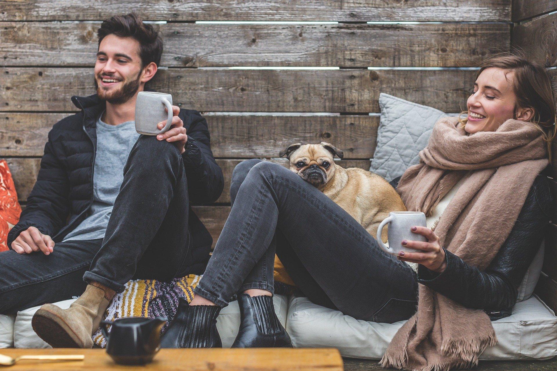 Un cuplu zâmbitor savurând câte o ceașcă de cafea