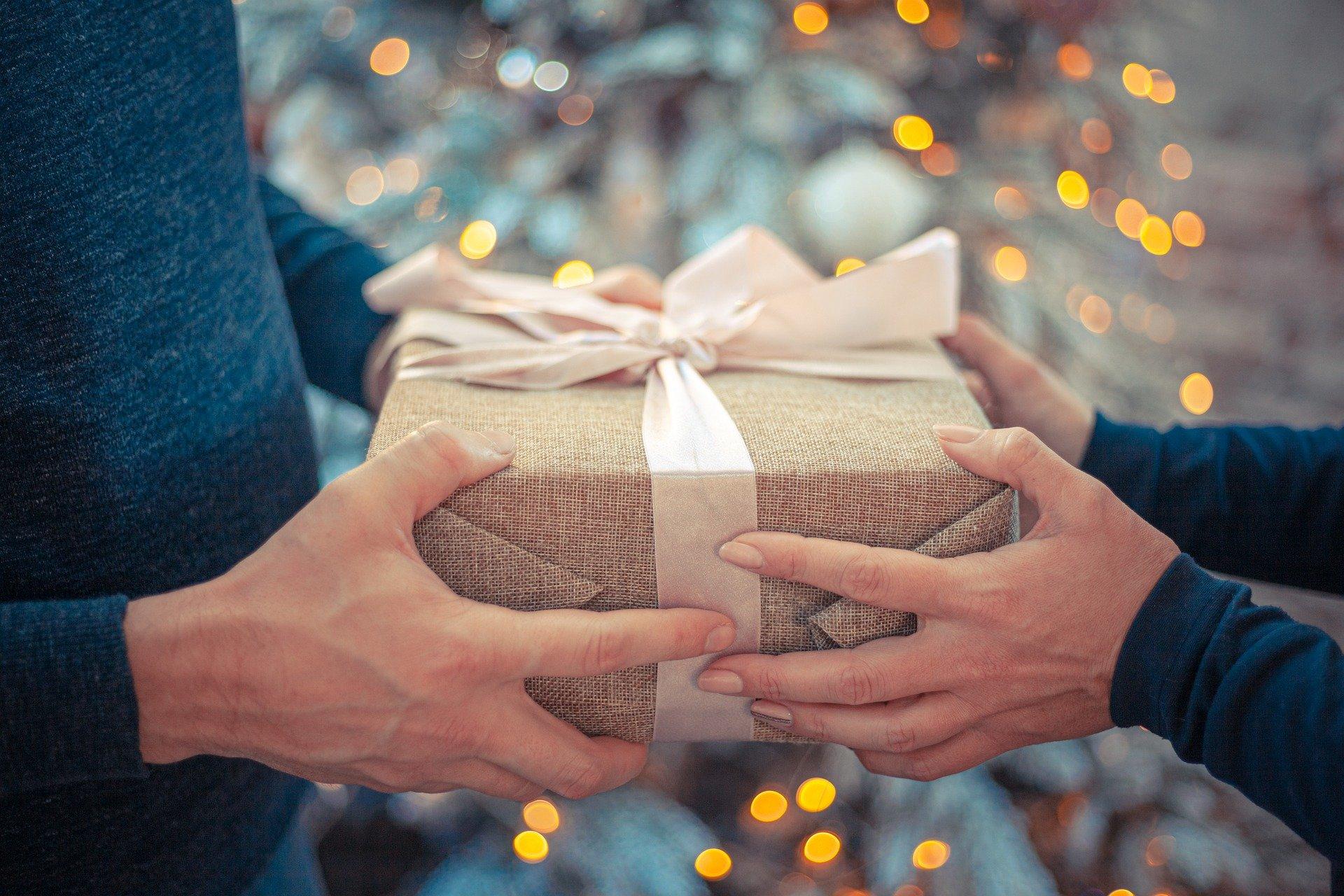 cadou de Craciun impachetat, cu mainile unui cuplu pe el