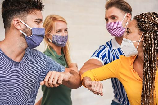 Tineri care poartă mască și se salută cu cotul