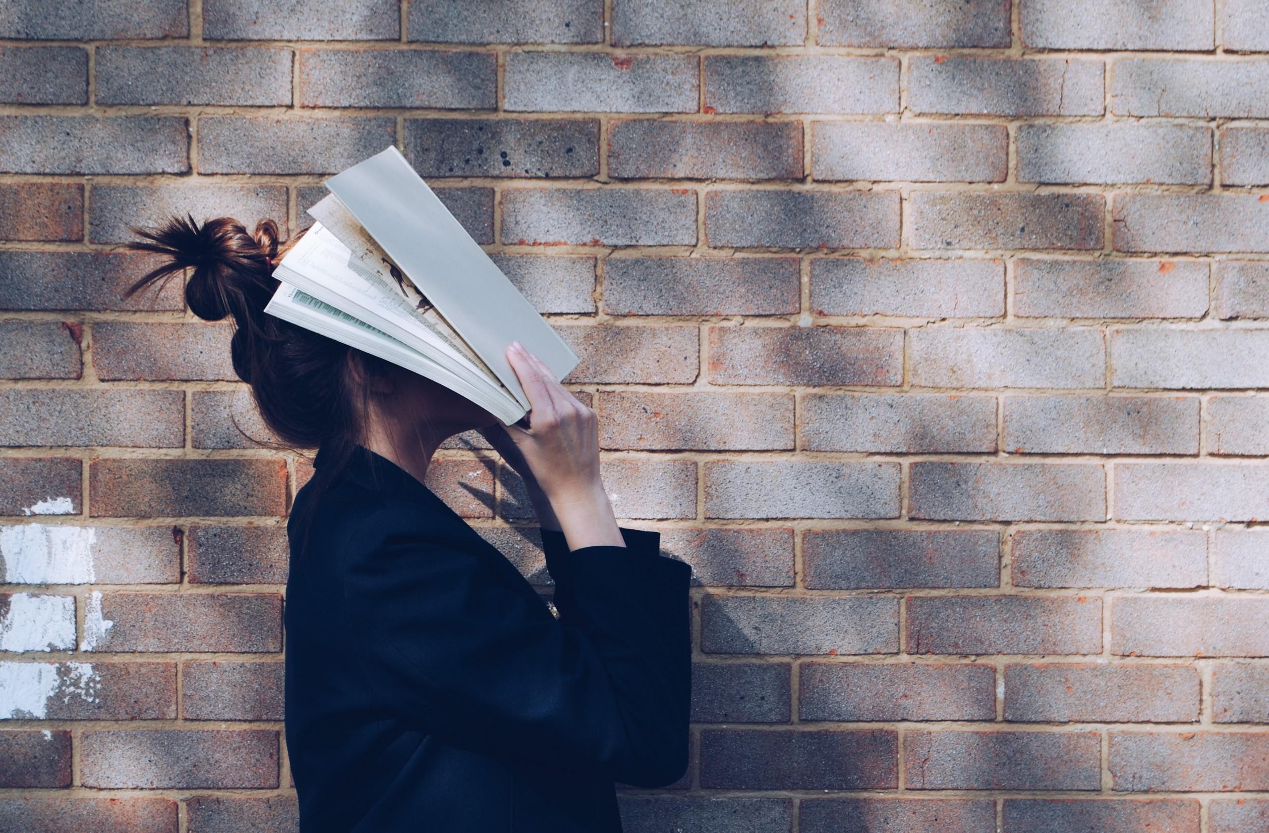 femeie care ține o carte pe față