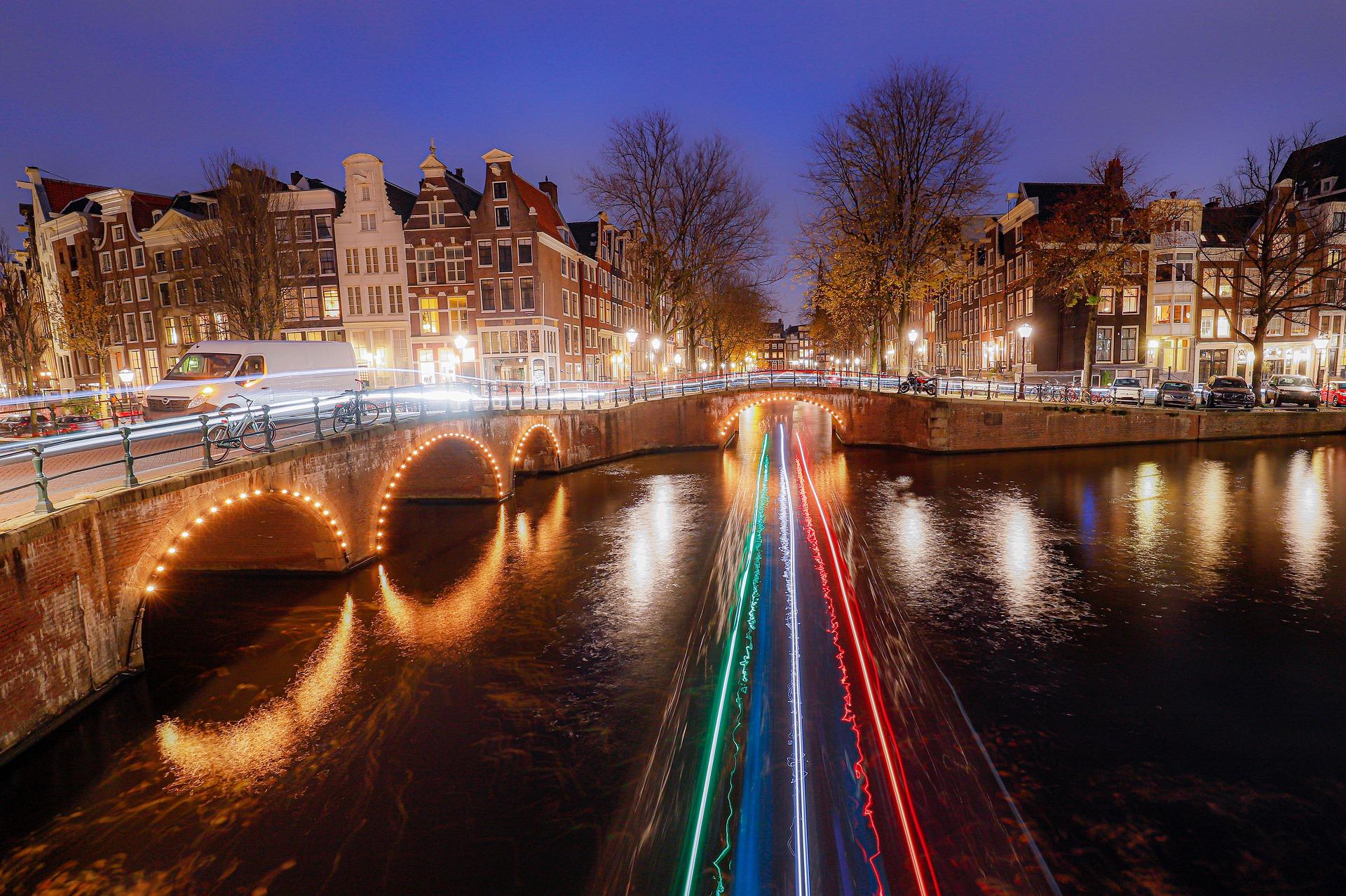 Peisaj nocturn din Amsterdam - un pod în stil tradițional, iluminat