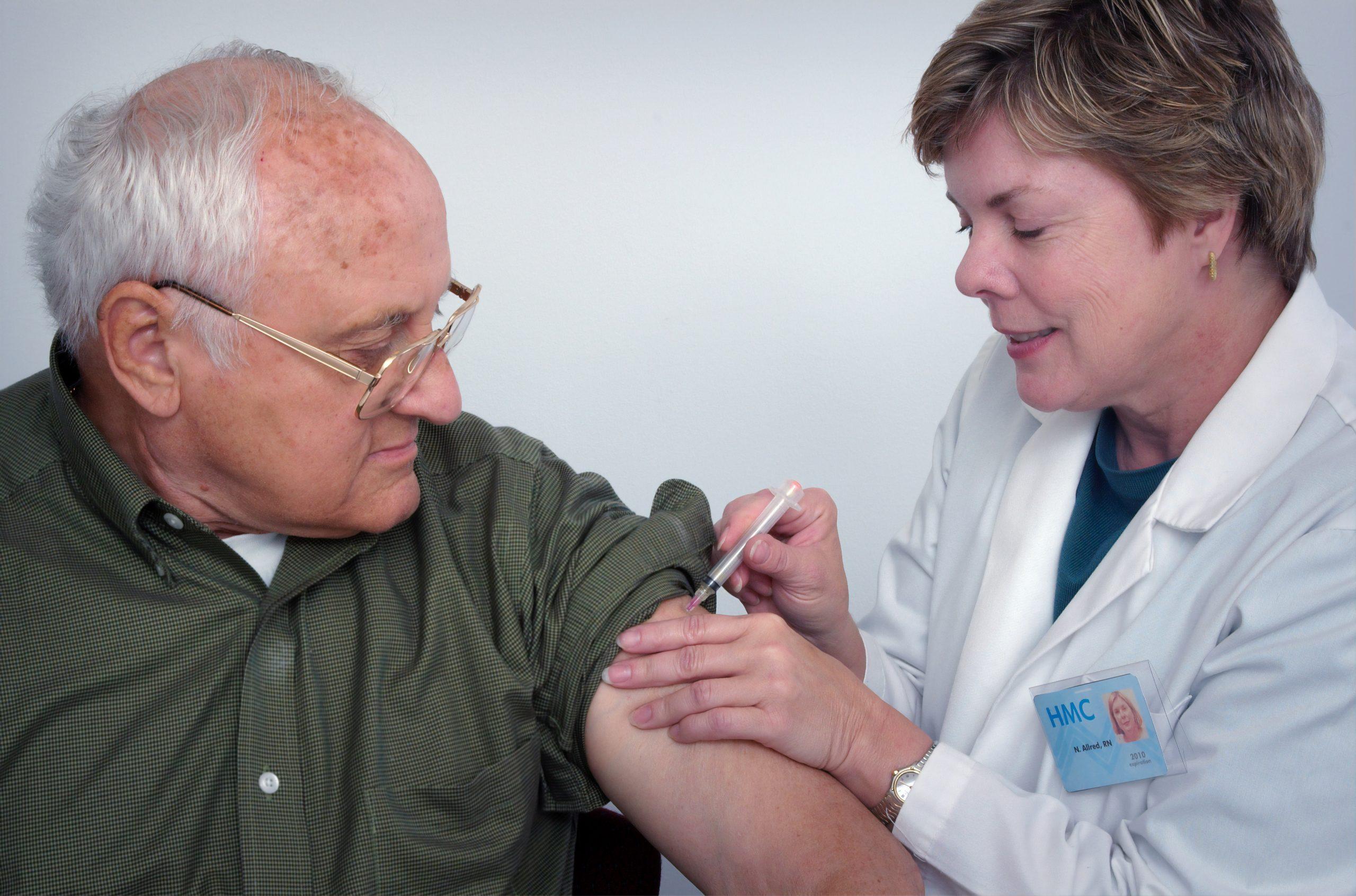 Bărbat în vârstă vaccinat de o asistentă medicală