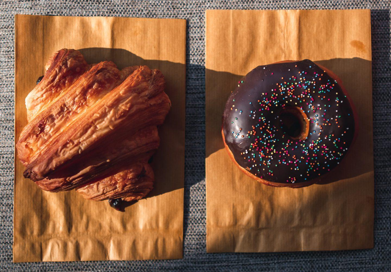 Un croissant și o gogoașă cu glazură de ciocolată, pe o masă
