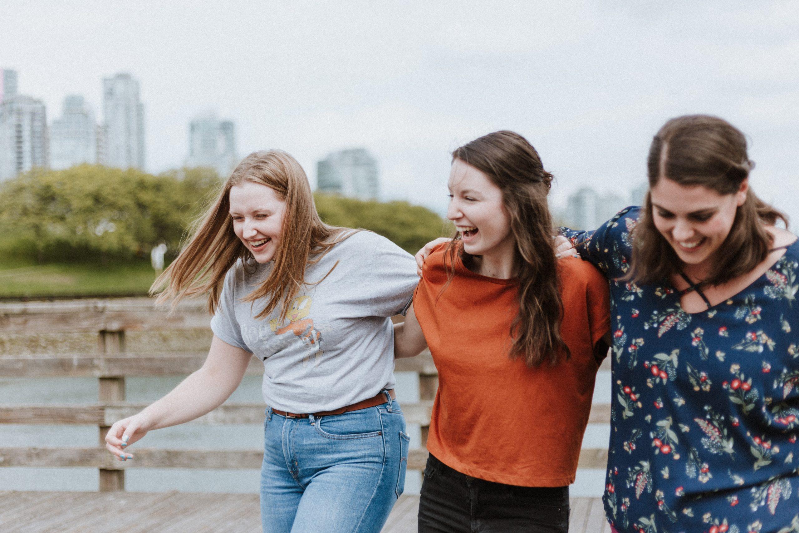 Trei fete zâmbind ți ținându-se în brațe