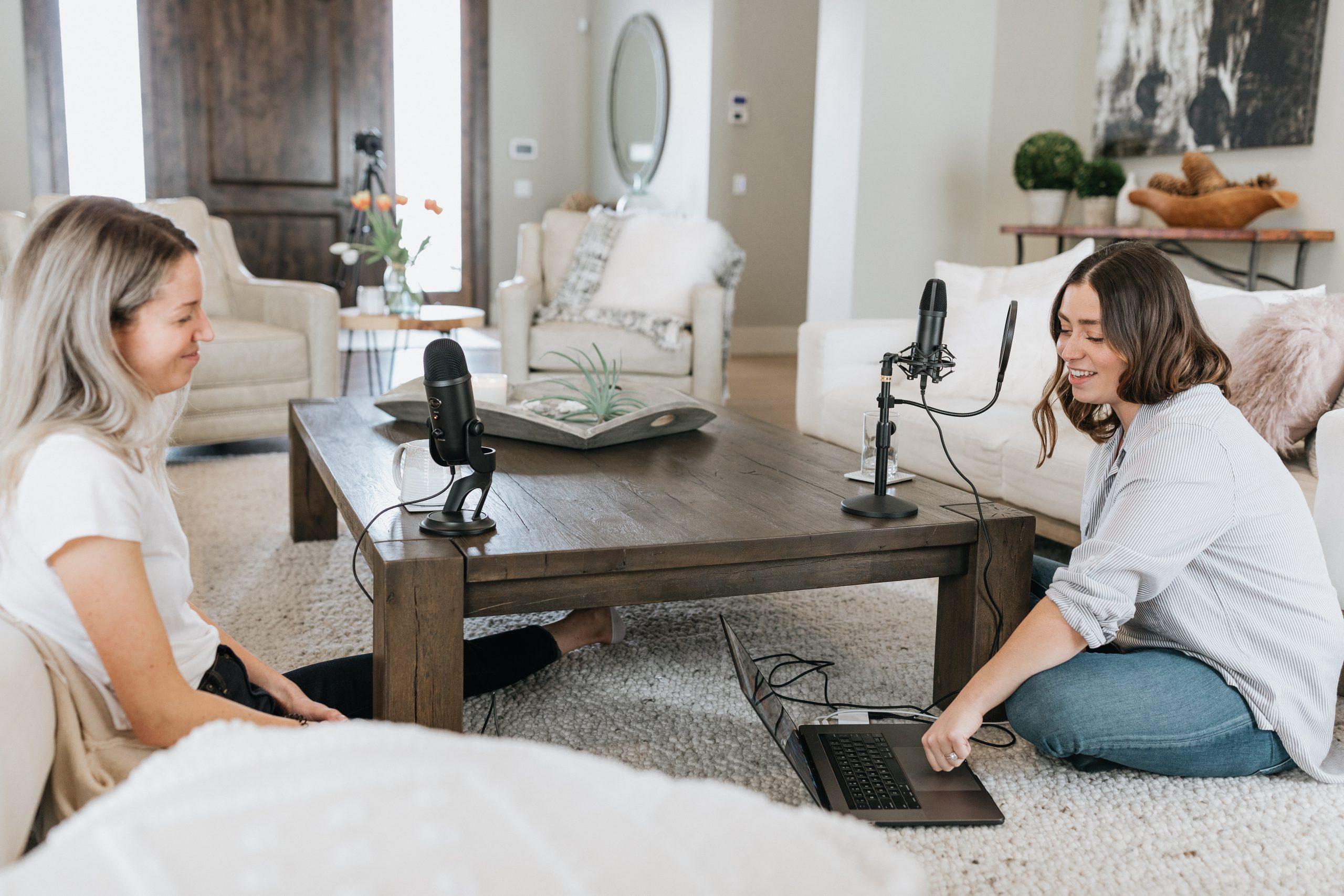 Două femei care înregistrează un podcast, așezate la o masă