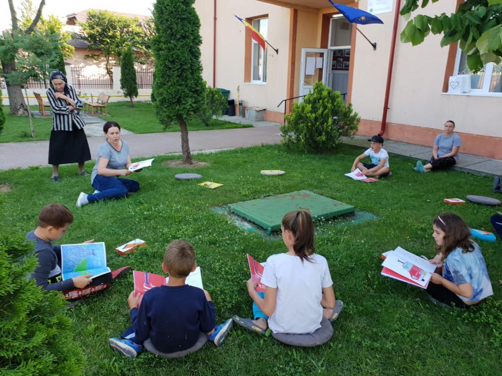 copii, in curte, citesc